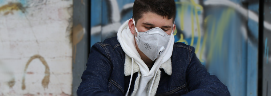 Man with a protective mask, sitting in front of a wall
